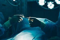 Zakończenie gloved ręki trzyma chirurgicznie nożyce obraz royalty free
