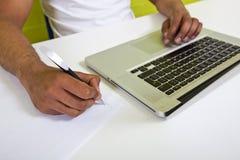 Zakończenie indianin up obsługuje ręki pisze na papierze obok laptopu Zdjęcia Stock