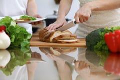 Zakończenie istota ludzka wręcza przecinanie chleb w kuchni Przyjaciele ma zabawę w kuchni podczas gdy gotujący Szefa kuchni kuch Zdjęcie Royalty Free