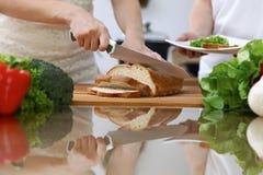 Zakończenie istota ludzka wręcza przecinanie chleb w kuchni Przyjaciele ma zabawę w kuchni podczas gdy gotujący Szefa kuchni kuch Zdjęcie Stock