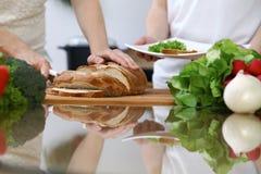 Zakończenie istota ludzka wręcza przecinanie chleb w kuchni Przyjaciele ma zabawę w kuchni podczas gdy gotujący Szefa kuchni kuch Obrazy Royalty Free