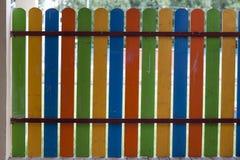 Zakończenie jaskrawy kolorowy błękit, zieleń, kolor żółty i pomarańczowy stubarwny drewniany niski dekoracyjny ogrodzenie outdoor zdjęcia royalty free