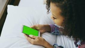 Zakończenie kędzierzawy mieszany biegowy kobiety lying on the beach w łóżku używa smartphone z zieleń ekranem w domu zbiory