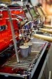 Zakończenie kawy espresso dolewanie od nowożytnej czerwonej kawowej maszyny fotografia stock