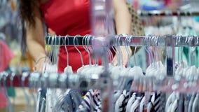 Zakończenie, kobiet ręki sortował out wiele wieszaki z strojami wybór i zakup odziewamy w sklepie na zakupy zbiory wideo
