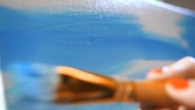 Zakończenie Kobieta maluje obrazek Piękni szczotkarscy ruchy z błękitną farbą na kanwie 4K zwalniają mo zbiory