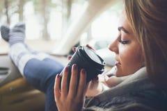 Zakończenie kobieta pije takeaway filiżankę kawy podczas wycieczki samochodowej w samochodzie Obraz Royalty Free