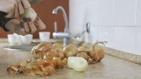 Zakończenie kobieta wręcza cebuli od plewy na kuchennym stole czysty Tylko hsnds zbiory