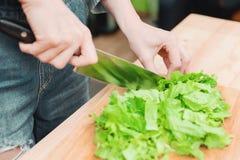 Zakończenie kobieta wręcza siekać zielonej rośliny w domu sałatkowa kulinarna sałatka od warzyw na drewnianej tnącej desce _ Zdjęcia Stock