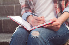 Zakończenie kobiety ręki writing na notatniku w parku Fotografia Royalty Free