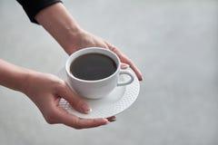 Zakończenie kobiety ` s ręka trzyma filiżankę gorąca kawa w biurze Zdjęcie Royalty Free