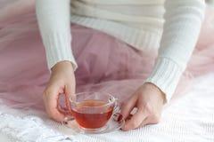 Zakończenie kobiety ` s up wręcza trzymać filiżankę herbata, być ubranym białego pulower i cieszyć się wolnego czas, Obrazy Royalty Free