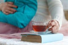 Zakończenie kobiety ` s up wręcza trzymać filiżankę herbata, być ubranym białego pulower i cieszyć się wolnego czas, Zdjęcie Stock