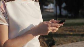 Zakończenie kobiety ` s up wręcza używać smartphone obsiadanie na ławce w parku przy zmierzchem Piękna Europejska dziewczyna text Zdjęcie Stock