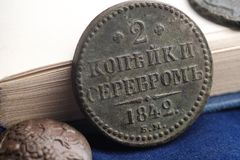 Zakończenie 2 kopiejki w srebrze 1842 Rosja, stary pieniądze od książki na błękitnym sukiennym tle fotografia stock