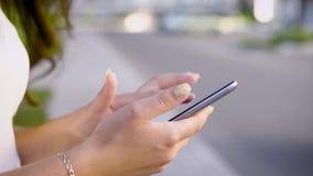Zakończenie który patrzeje fotografie na telefonie komórkowym, up strzelał s kobiety ` ręki dama jedzie jej palec przez zbiory