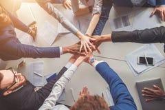 Zakończenie ludzie trzyma ręki wpólnie podczas gdy siedzący wokoło biurka Zdjęcia Stock