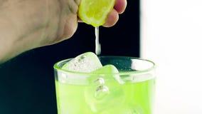 Zakończenie mężczyzna ściśnięcia żółta cytryna na napoju alkoholu koktajlu w szkło z kostkami lodu, zabawa klubu światło zbiory