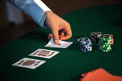 Zakończenie mężczyzna ręka otwiera karty przy grzebaka stołem z a zdjęcie stock