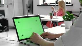 Zakończenie mężczyzna ` s Wręcza działanie na zieleń ekranie na laptopie W tła Zamazującym i Jaskrawy Zaświecającym biurze dokąd  zdjęcie wideo