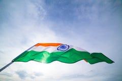Zakończenie mężczyzna up ręka trzyma India flaga na niebieskiego nieba tle fotografia stock