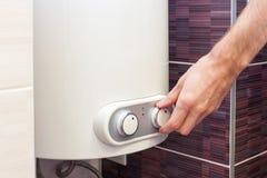 Zakończenie mężczyzna wręcza ustawiać temperaturę woda w Elektrycznym bojlerze Fotografia Stock