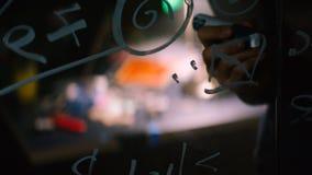 Zakończenie mężczyzna writing formuły na szklanym whiteboard zapas Zakończenie naukowa writing na szklanej formule zdjęcie stock