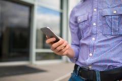 Zakończenie mężczyzna z komórką na zamazanym miastowym tle Urzędnik dzwoni telefon pojęcia odosobniony technologii biel kosmos ko Zdjęcie Stock