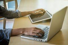 Zakończenie męska ręka, używać cyfrową pastylkę i komputer podczas gdy s Fotografia Stock