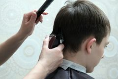 Zakończenie męski ostrzyżenie Żeńskie ręki fryzjer z drobiażdżarką i czarną gręplą, robią fryzurze na faceta ` s przewodzić fotografia stock