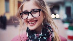 Zakończenie młoda śliczna dziewczyna ono uśmiecha się charmingly z hełmofonami up wyprostowywa w kierunku kamery, przypadkowa fry zbiory wideo