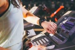 Zakończenie młoda Kaukaska kobiety ` s ręka w gym używa sporta zegarek, czarny pulsu nadgarstek z tyłu karuzeli w sp obrazy royalty free