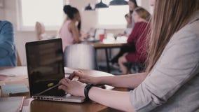 Zakończenie młoda kobieta freelance pracownik pisać na maszynie na laptopie stołem w ruchliwie nowożytnej coworking przestrzeni z