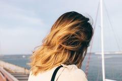 Zakończenie młoda kobieta patrzeje denną pozycję na bulwarze Obraz Stock