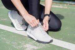 Zakończenie młoda kobieta up zasznurowywa up jej but przygotowywającego trening na ćwiczyć w parku z ciepłym lekkim światłem słon Zdjęcie Royalty Free