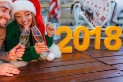 Zakończenie młoda para jest ubranym Santa kapelusze, trzyma szkła z szampanem w ich rękach, łączyć głowy, kłama dalej obraz royalty free