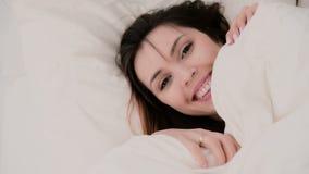 Zakończenie młoda piękna kobieta z śmiesznym spojrzeniem chuje pod koc Dziewczyna ma zabawę w łóżku zdjęcie wideo