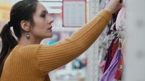 Zakończenie młodej kobiety s twarz w supermarkecie Dziewczyny wybierać odziewa przy półkami z rozważną twarzą 4K zbiory wideo