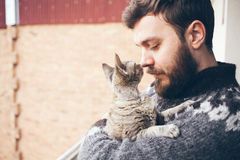 Zakończenie młody człowiek który stoi na balkonie z jego kotem Fotografia Stock