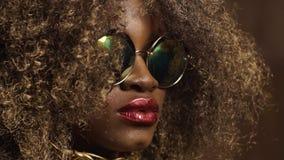 Zakończenie magiczny złoty amerykanin afrykańskiego pochodzenia kobiety model w masywnych okularach przeciwsłonecznych z jaskrawy zbiory wideo