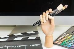 Zakończenie mannequin ręka z makeup krzakami, kolorowa makeup paleta, clapboard na stole Obraz Stock