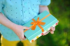 Zakończenie miło zawijający urodzinowy prezent trzyma dzieckiem Zdjęcia Stock
