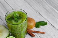 Zakończenie naturalny zielony napój od kiwi z mennicą na szarym drewnianym tle składniki organiczne obraz royalty free