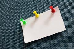 Zakończenie nutowy papier i wiele kolorów pushpin w błękitnego corkboard obrazy royalty free