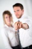 Zakończenie obrazek rozochoceni młodzi pośrednik handlu nieruchomościami pary mienia domu klucze Fotografia Stock