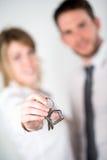 Zakończenie obrazek rozochoceni młodzi pośrednik handlu nieruchomościami pary mienia domu klucze Obrazy Stock
