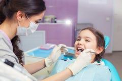 Zakończenie otwiera jego usta szerokiego podczas taktować jej zęby dentystą ładna mała dziewczynka Obraz Stock