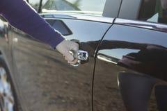 Zakończenie otwiera samochodowego drzwi kobiety ręka zdjęcie stock