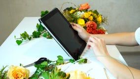Zakończenie pastylka na którym wręcza ołowianych palce am kwiaciarni dziewczyny ` s zdjęcia stock