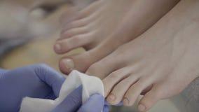 Zakończenie pedikiurzysta w rękawiczkach wyciera klientów gwoździe z pieluchą zbiory